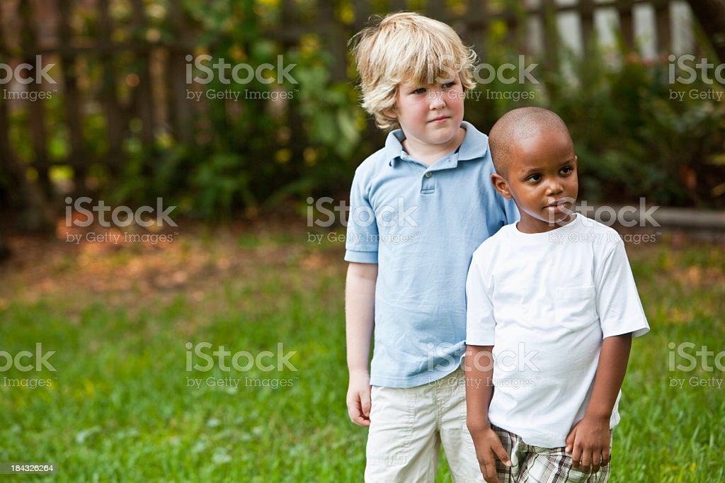 Two little boys in back yard stock photo