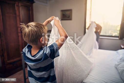 Little boys aged 8 are making bed together.