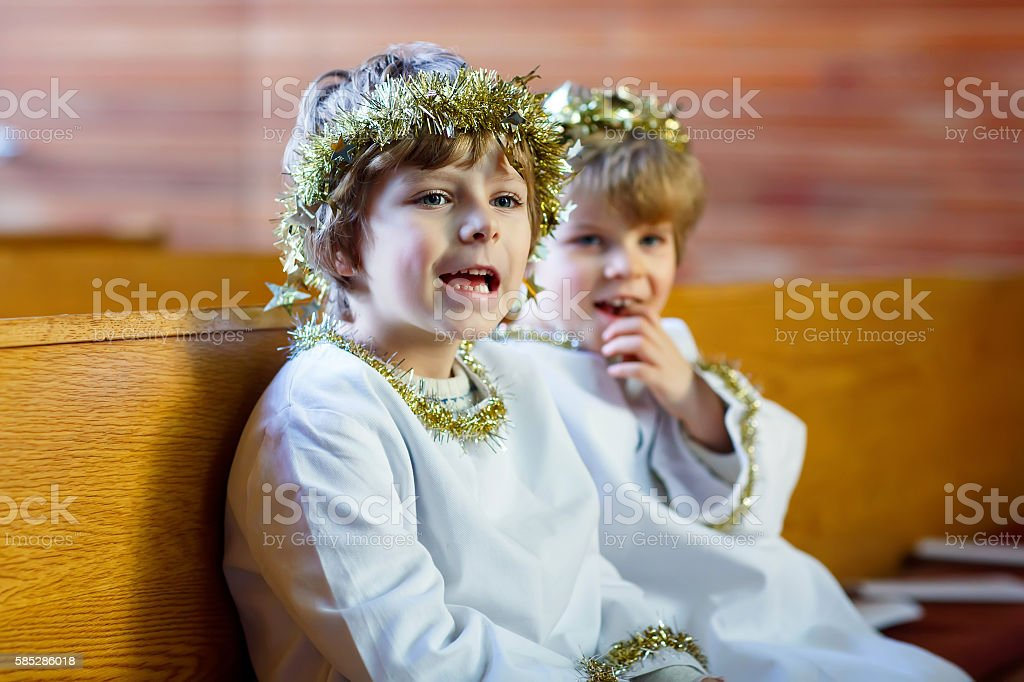 Two little boys playing angel of Christmas story in church stock photo