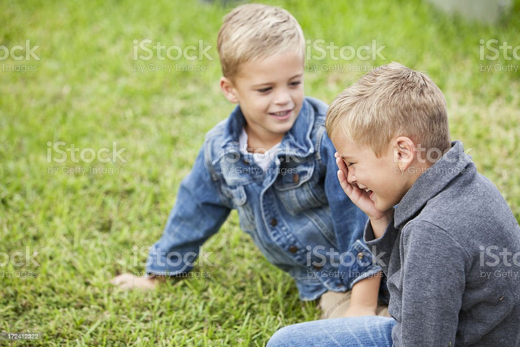 Two little boys playing on grass stock photo