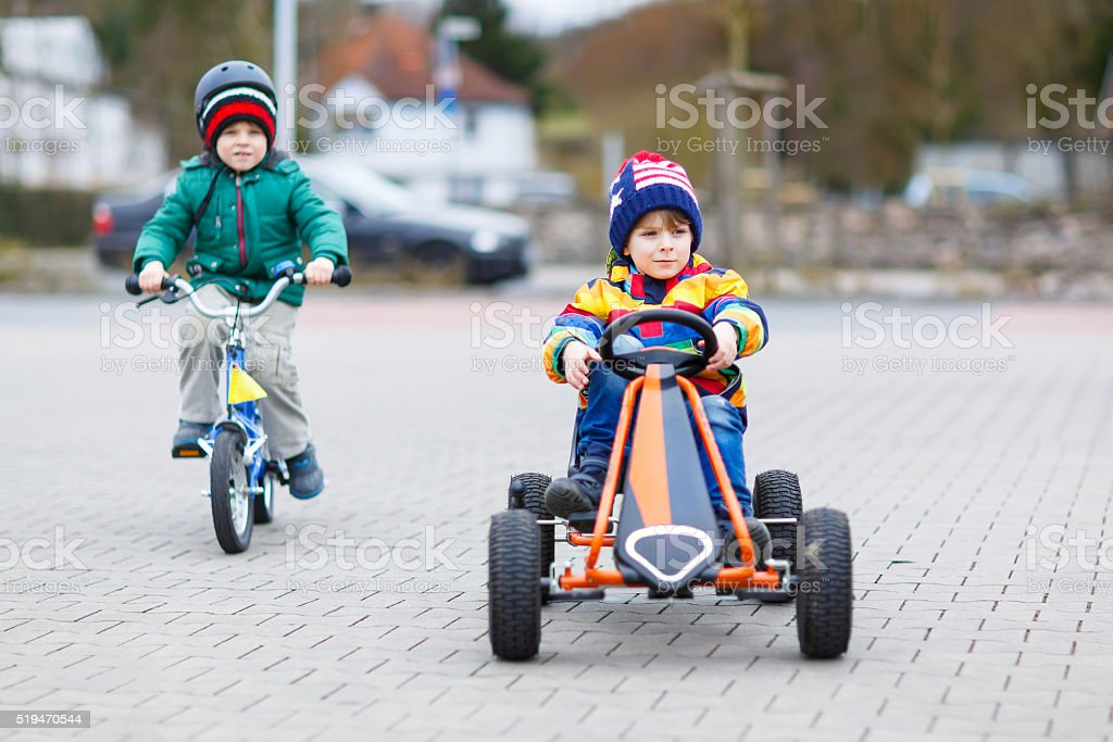 Two little boys playing with race car and bicycle stock photo