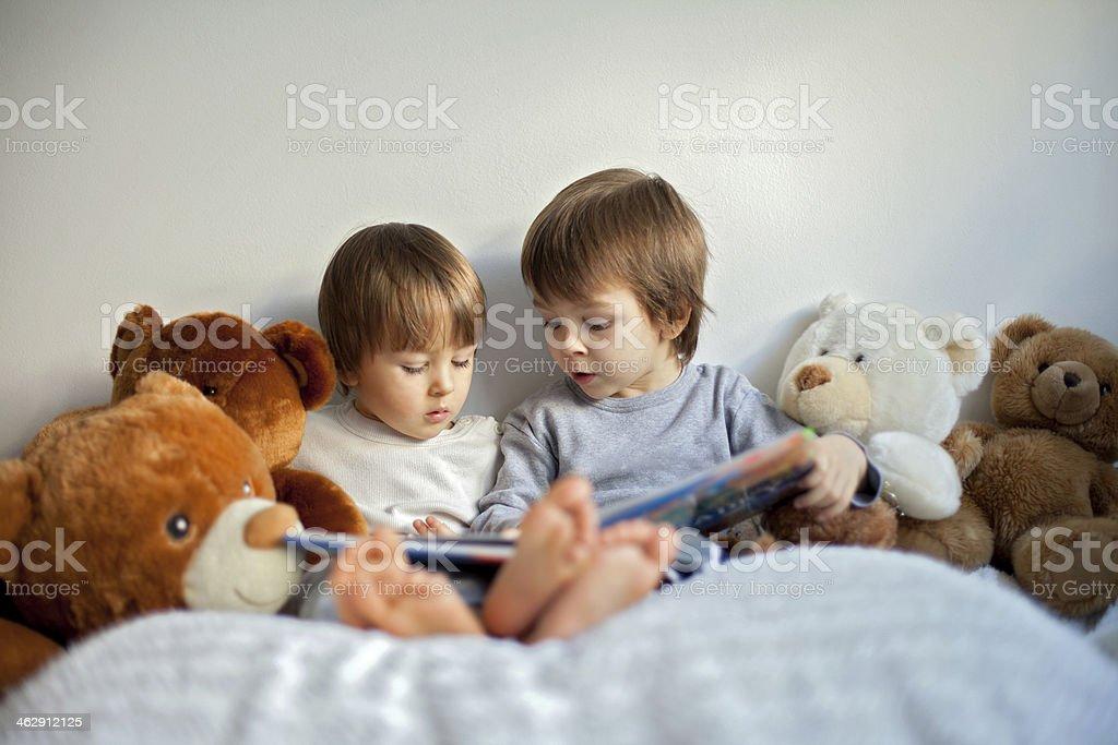 Two little boys, reading a book, having fun stock photo