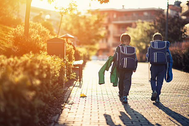 two little boys returning from school - back to school stock photos and pictures