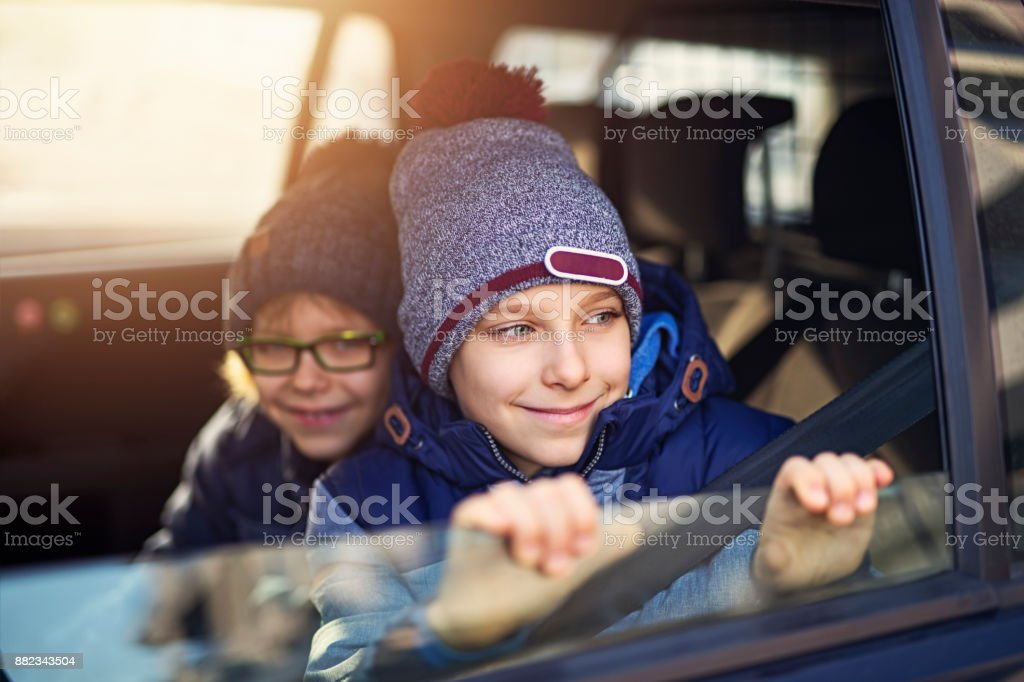 Two little boys riding to school in car stock photo