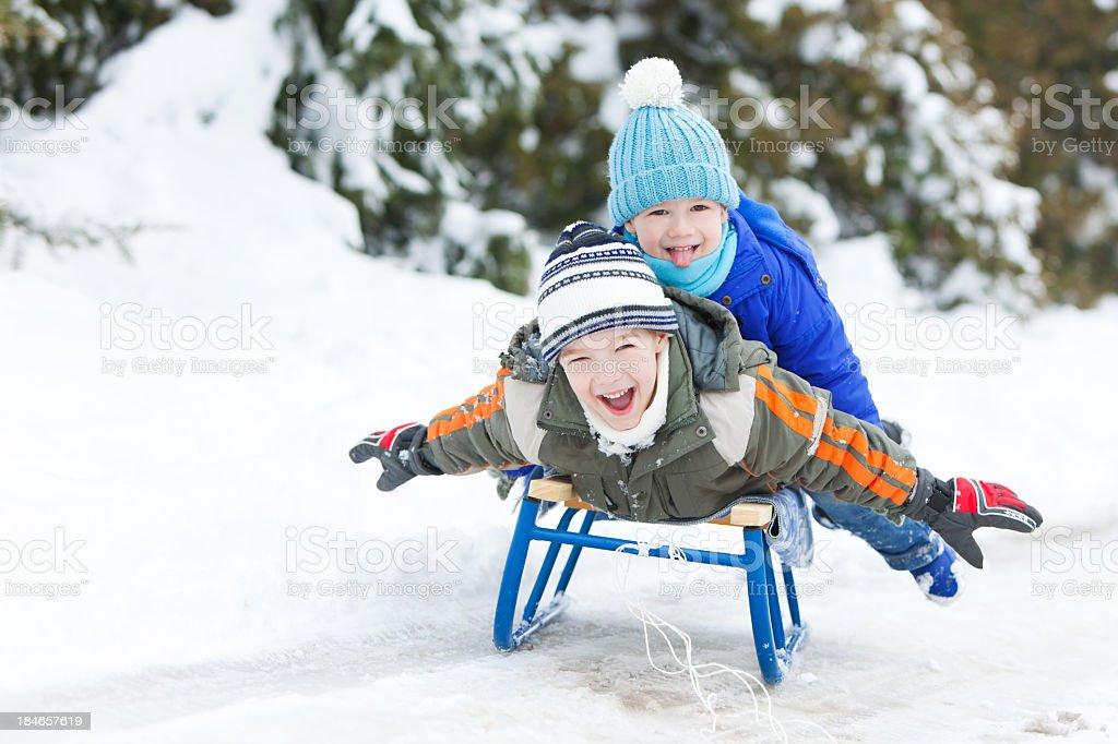 Two Little Boys Sledding On Snow royalty-free stock photo