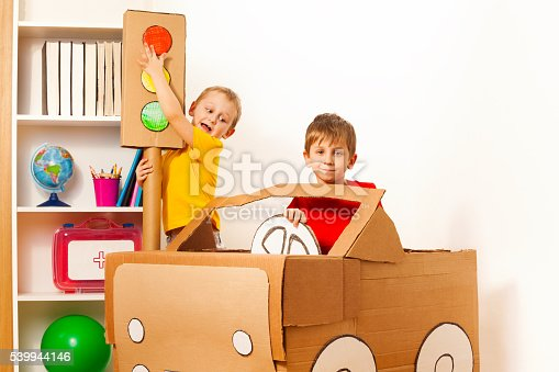 496487362 istock photo Two little boys studying road rules with toy light 539944146