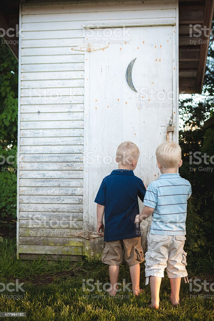 Two little boys waiting to enter outhouse to go potty stock photo