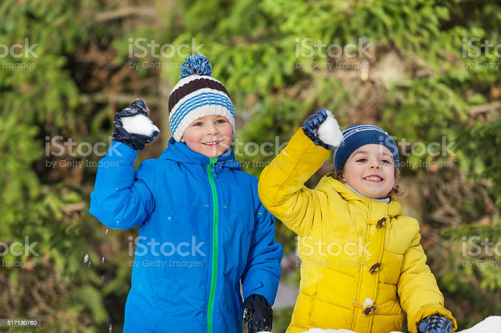 Two little boys with snowballs in the park stock photo