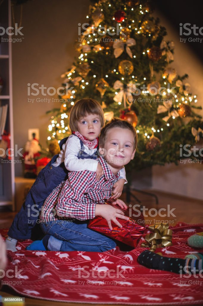 two little brothers opening christmas presents royalty free stock photo