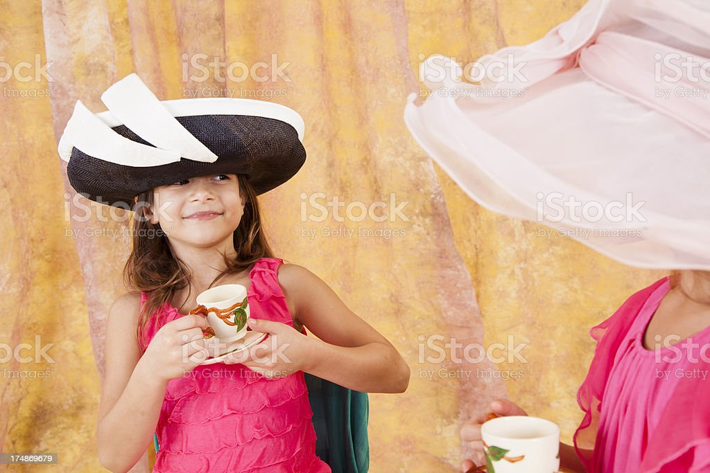 Two little Caucasian girls 7-8, playing tea party hats teacup royalty-free stock photo