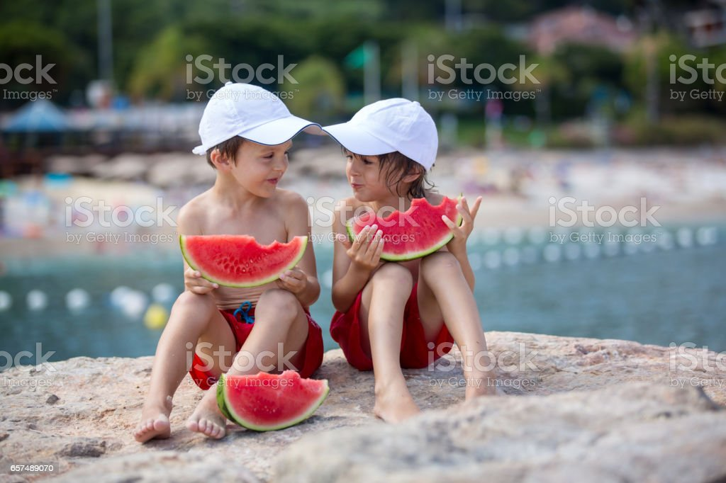 Two little children, boy brothers, eating watermelon on the beach, summertime stock photo