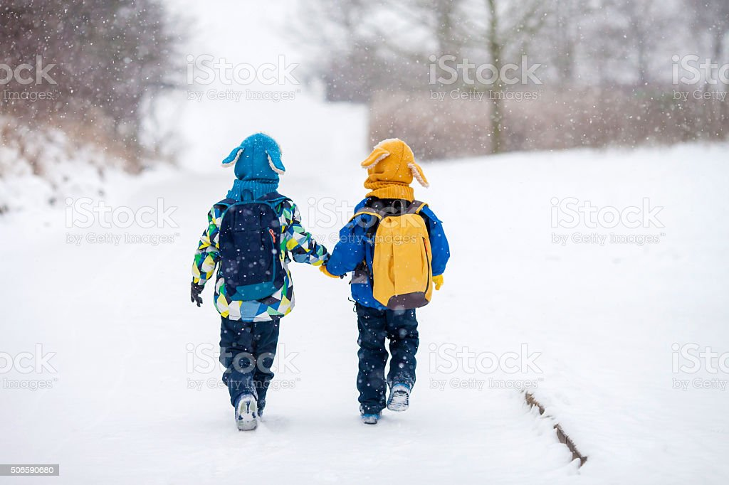 Two little children, boy brothers with backpacks in the park stock photo