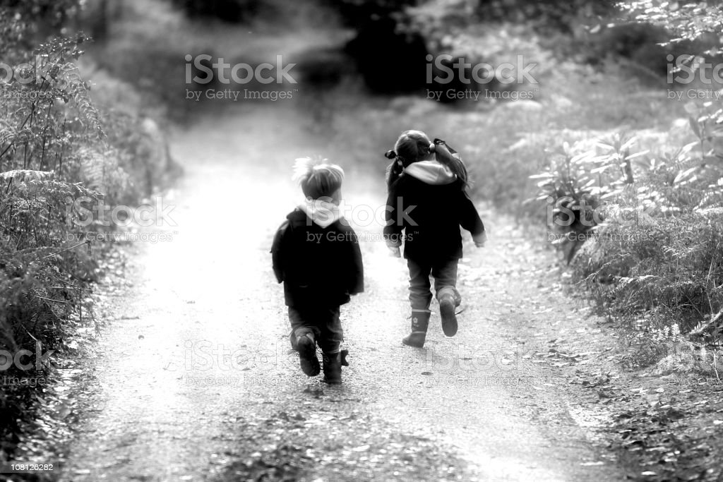 Two Little Children Running Down Dirt Road, Black and White royalty-free stock photo