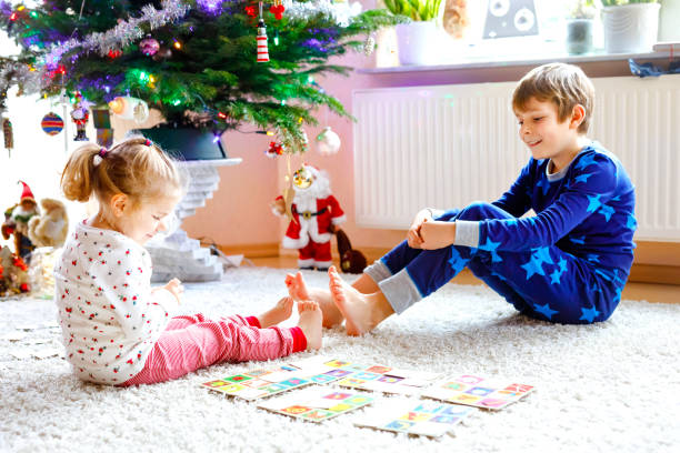 Two little chilren, cute toddler girl and school kid boy playing together card game by decorated Christmas tree. Happy healthy siblings, brother and sister having fun together. Family celebrating xmas stock photo