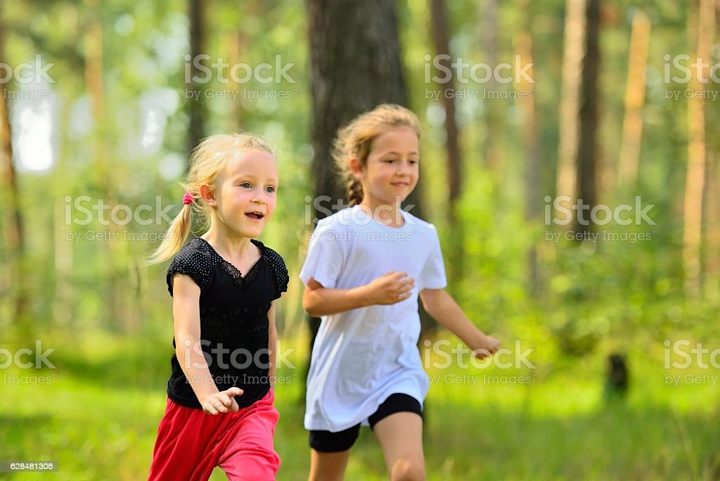 Two little cute girls jogging in forest стоковое фото