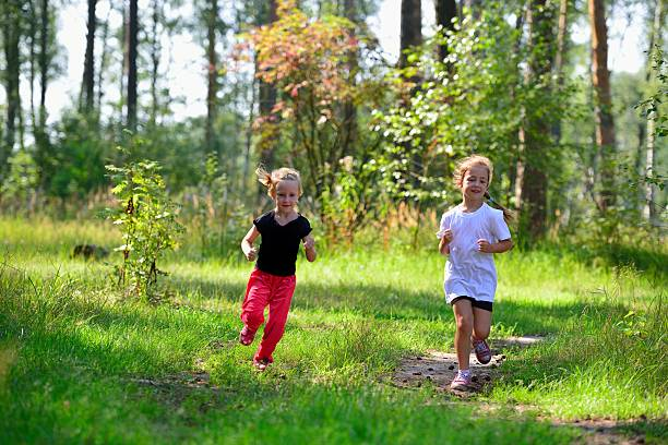 Cтоковое фото Two little cute girls jogging in forest