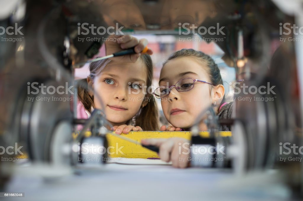 Two little engineers working in team while repairing a robot. stock photo