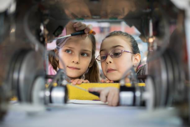 zwei kleine ingenieure im team zu arbeiten, während der reparatur eines roboters. - schule der zukunft stock-fotos und bilder