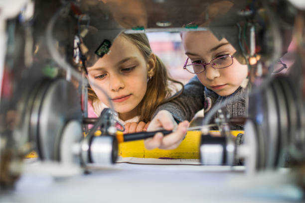 Two little engineers working in team while repairing a robot. - foto stock