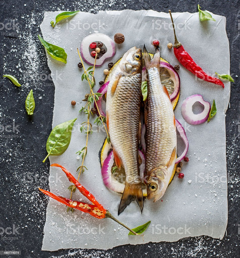 Two Little Fresh River Fish On A Sheet Of Parchment Stock Photo