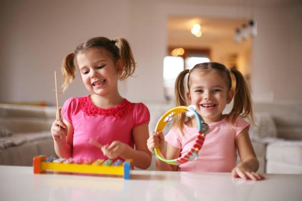 two little girl at music school. - lautbildungsspiele stock-fotos und bilder