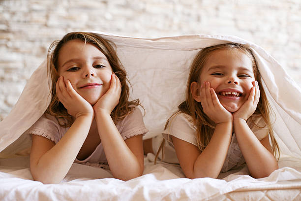 Two little girl in bed. Two little girl laying in bed and looking at camera. sister stock pictures, royalty-free photos & images