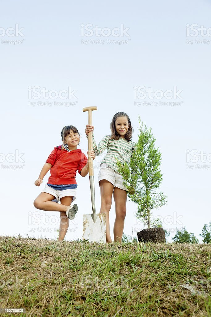 Two little girls about to plant a tree royalty-free stock photo
