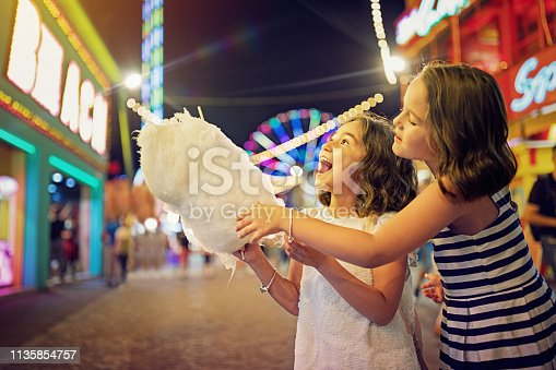 Two little girls are eating cotton candy at the fun fair and making fun