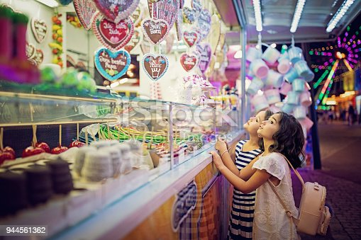 Two little girls are looking sweets in the candy wagon at the fun fair