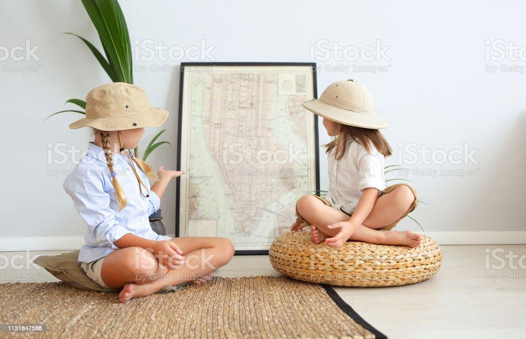 Dos niñas están jugando en casa a los viajeros que llevan ropa de estilo vintage - Foto de stock de Adulto joven libre de derechos