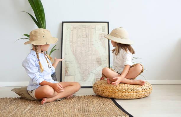 Dos niñas están jugando en casa a los viajeros que llevan ropa de estilo vintage - foto de stock