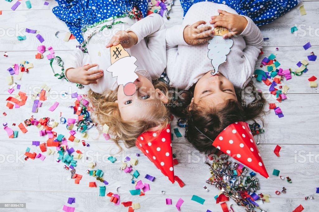 Dos pequeñas niñas niño moda colorido confeti en el piso y sombreros de fiestas lindos y hermosos con un helado pintado - foto de stock
