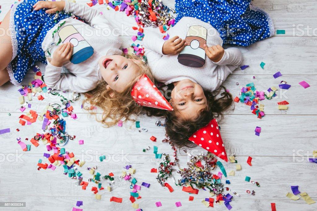 Dos poco niñas niño moda colorido confeti en el piso y en las tazas de papel pintado lindo y hermoso sombrero festivo - foto de stock