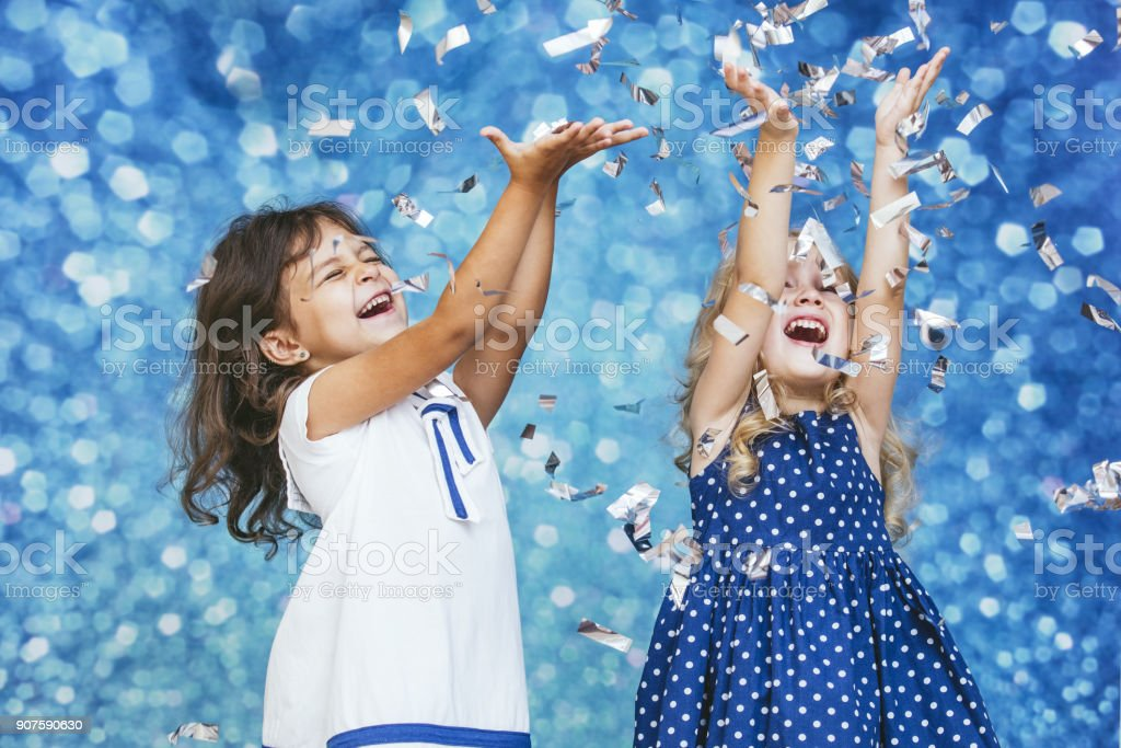 Two little girls child fashion with silver confetti in the background with patches of cute and beautiful stock photo