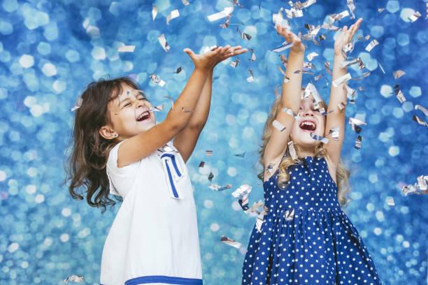 zwei kleine mädchen kind mode mit silbernen konfetti im hintergrund mit flecken von niedlich und schön - festliche babymode junge stock-fotos und bilder