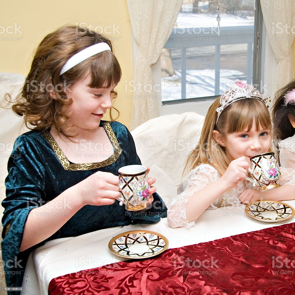 Two Little Girls Dressed as Princesses and Having Tea Party royalty-free stock photo