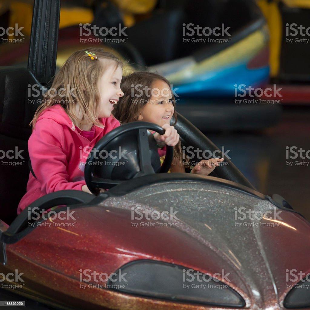 Two little girls having fun riding bumper cars stock photo