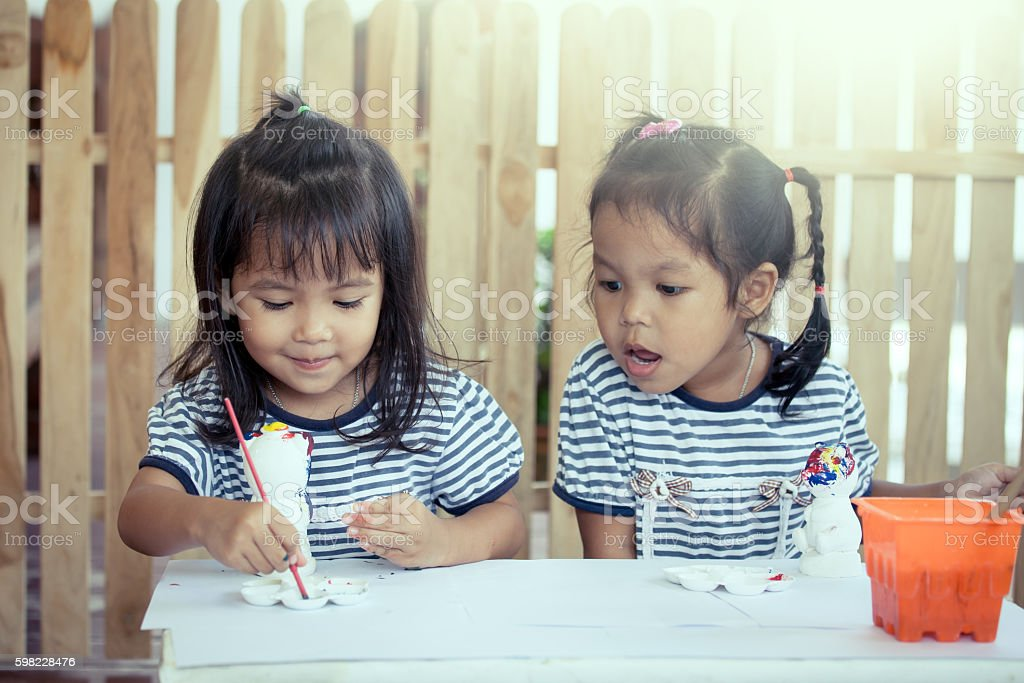 two little girls having fun to paint on stucco doll foto royalty-free