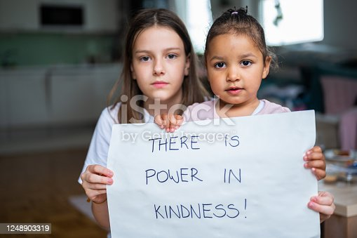 Two little girls, one caucasian and one african-american, holding a poster with handwritten message: There is power in kindness! They are in a domestic room and they are looking at camera.