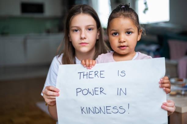 Zwei kleine Mädchen halten ein Poster mit handschriftlicher Botschaft: Es gibt Macht in Freundlichkeit! – Foto
