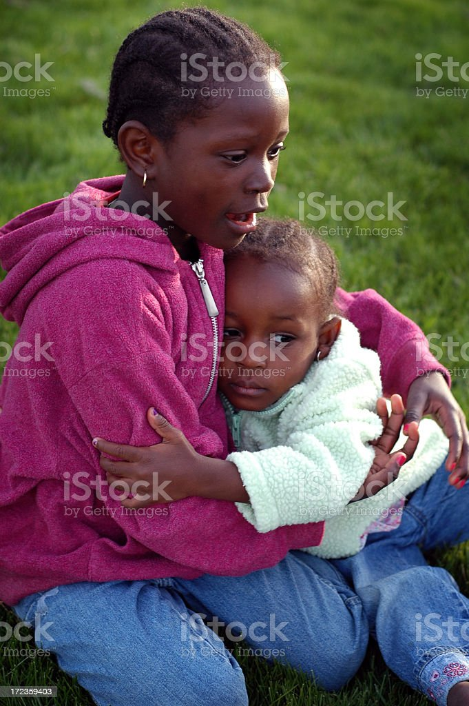 Two Little Girls Hugging Each Other Outside royalty-free stock photo