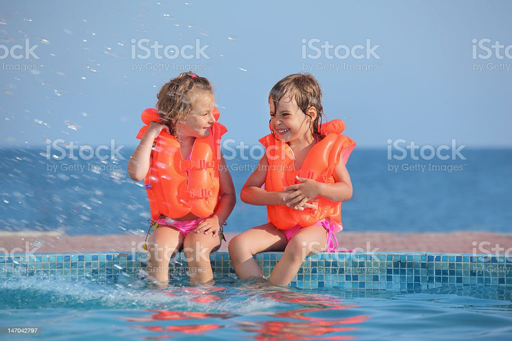 Two little girls in life-jackets sitting on ledge pool royalty-free stock photo