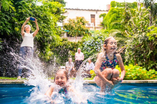 Two little girls jumping into a swimming pool stock photo
