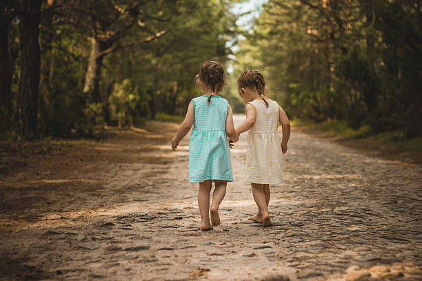 Two little girls on a forest road Photo of two cute twins walking along a forest road sister stock pictures, royalty-free photos & images