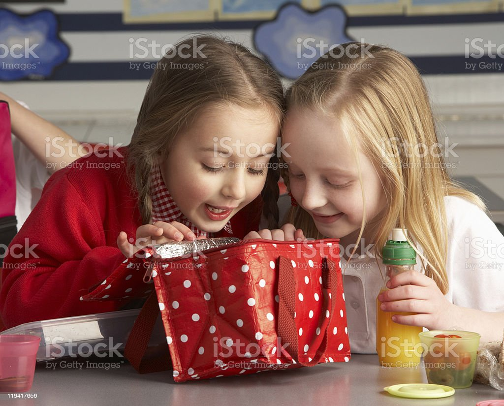 Two little girls peeking into lunch bag in class stock photo