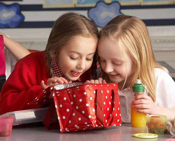 Two little girls peeking into lunch bag in class stock photo
