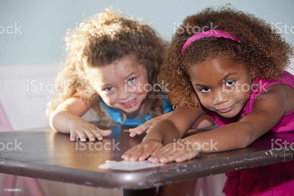 Two little girls playing at table stock photo