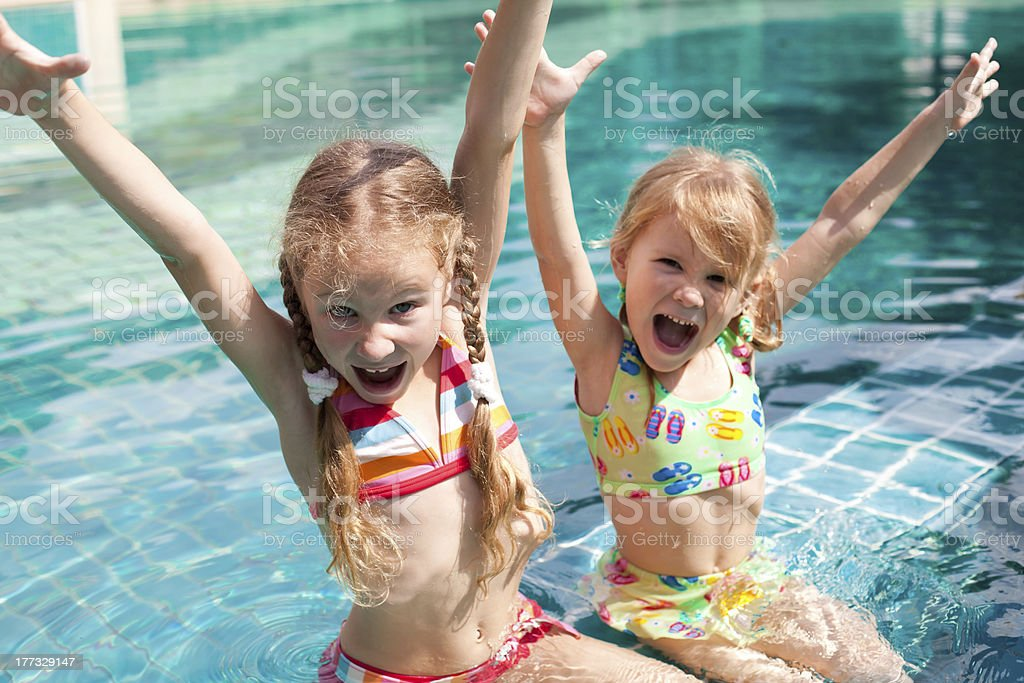 two little girls playing in the pool stock photo