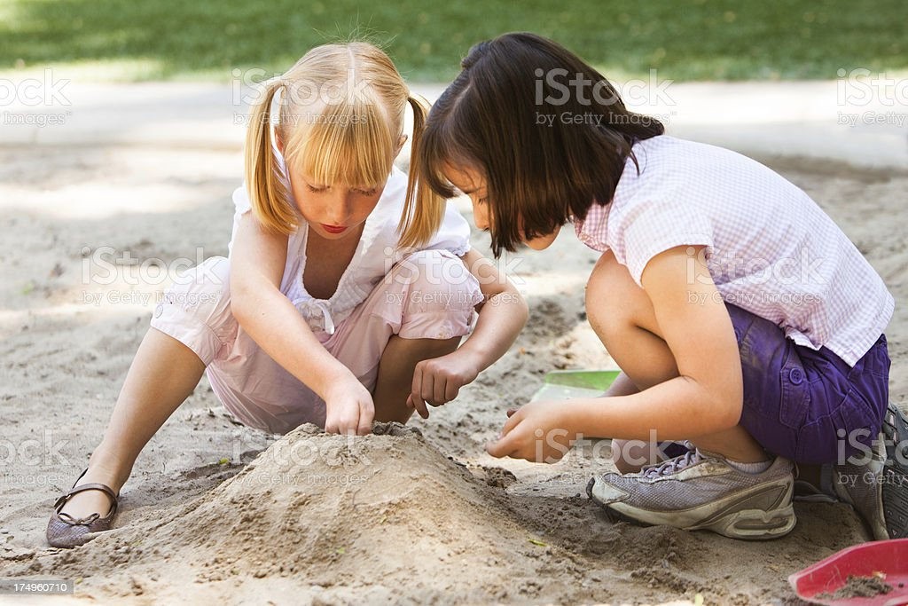 Two little girls playing in the sandbox stock photo