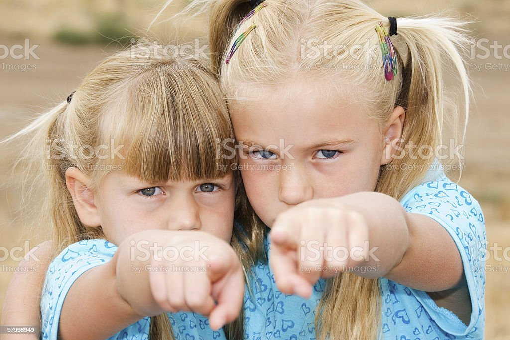 Two little girls pointing at the camera royalty-free stock photo